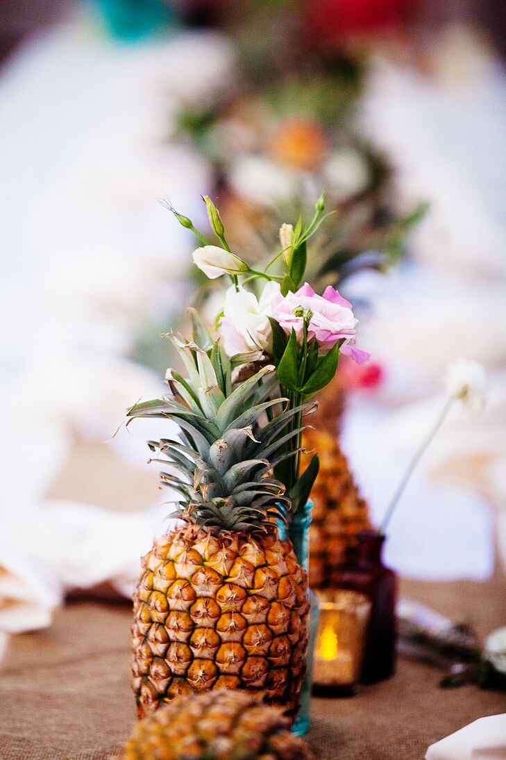 The ceremony aisle was lined with full pineapples along with small, simple flower arrangements. The middle of the aisle was sprinkled with petals and the natural sand.
