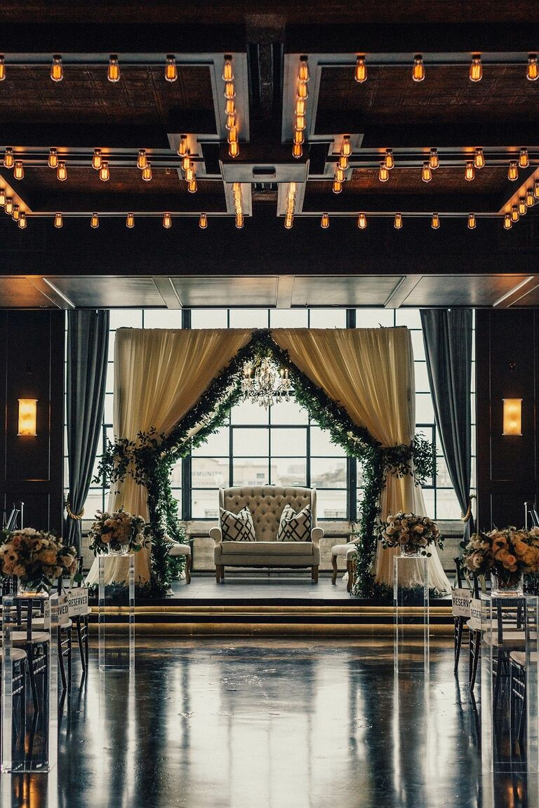 Mandap with cream draping and greenery garland accents