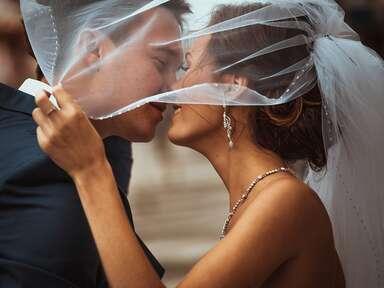 bride and groom kissing under veil