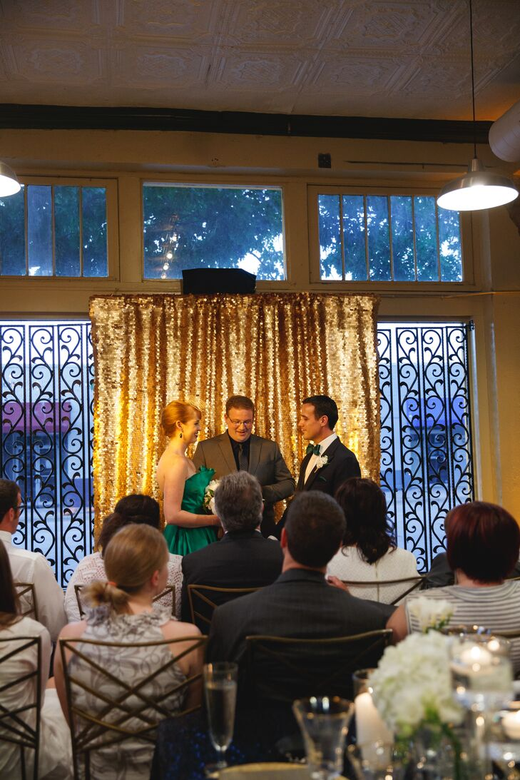 Angela and Ben wanted a candlelit ceremony, so they chose the unconventional route of having their dinner first and the ceremony after. They had a gold sequin background draped on the windows of the venue, and lots of vases with candles on each side of the altar. Guests were seated in two semi-circles.