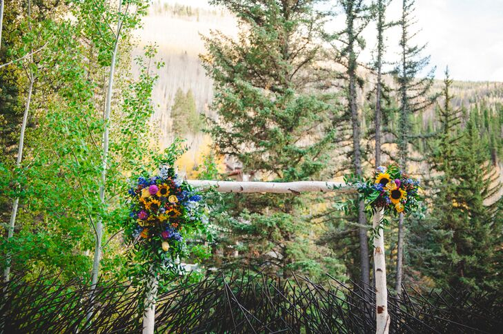 Kimberly and Charles exchanged vows under an Aspen wedding arch that florist Vintage Magnolia adorned with sunflowers, dahlias, hypericum berries and roses.