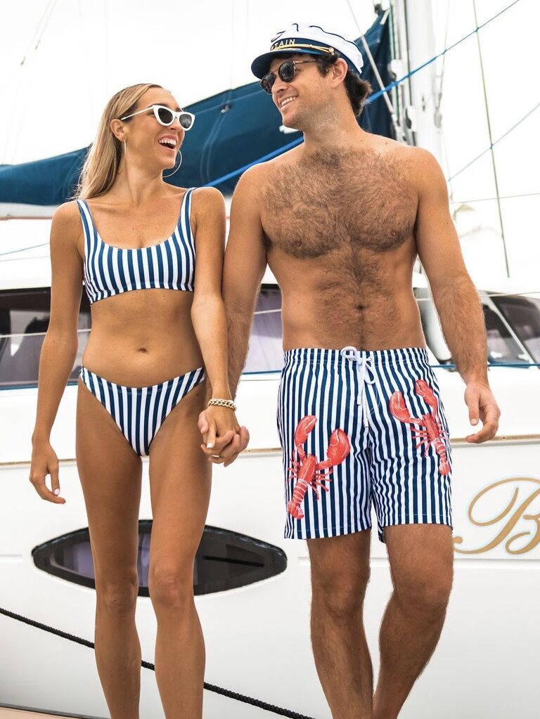 Couple holding hands in front of a yacht wearing matching nautical stripe swimwear