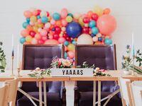 wedding sweetheart table with balloon backdrop and greenery