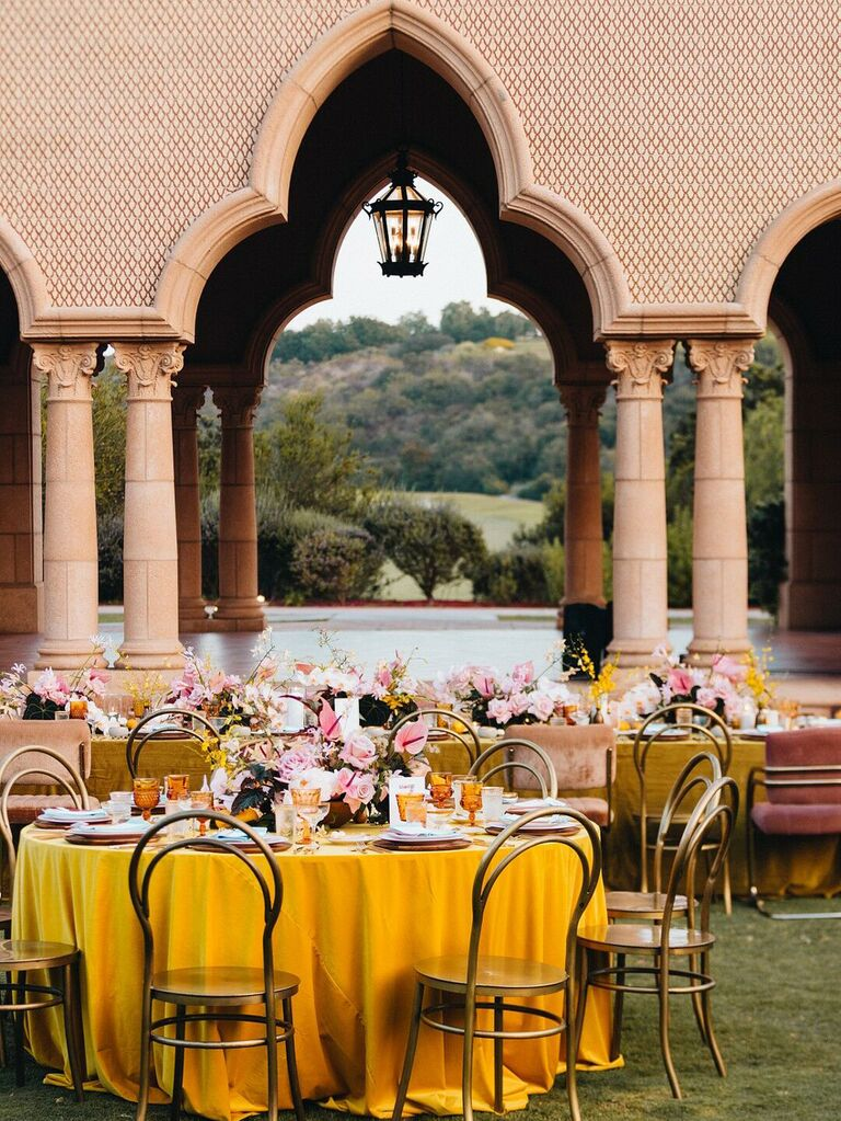 Multicultural wedding reception with yellow tablecloths and pink accents