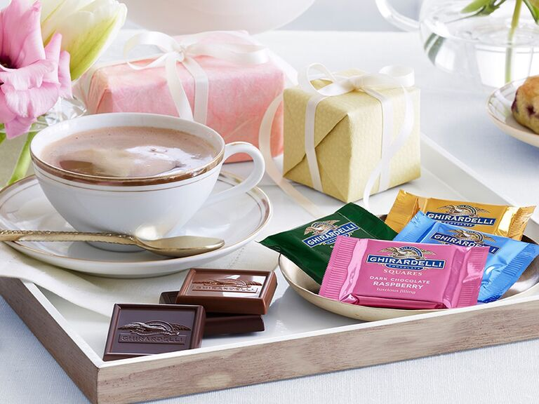 Ghirardelli chocolates on tray with hot chocolate and small gift boxes