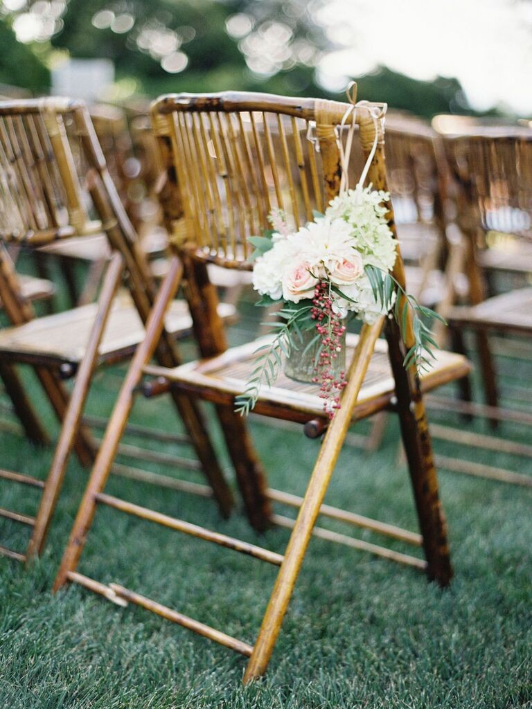 Bundle of florals with twine tied to ceremony chairs at barn wedding