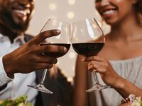 Couple toasting glasses of red wine