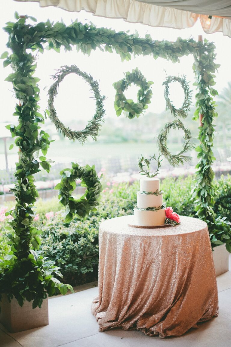 White wedding cake with green wreaths