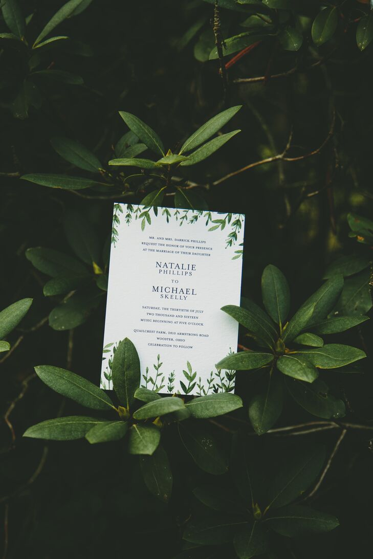 Simple white invitations decorated in greenery set the tone for a casual yet elegant garden party.
