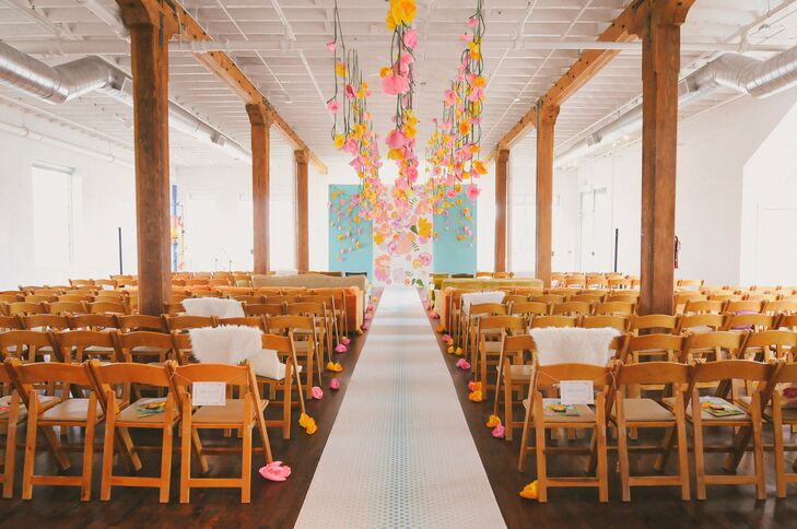 Hundreds of pink and yellow paper flowers hung on vines over the aisle, adding a unique and memorable accent to the mod ceremony decor.