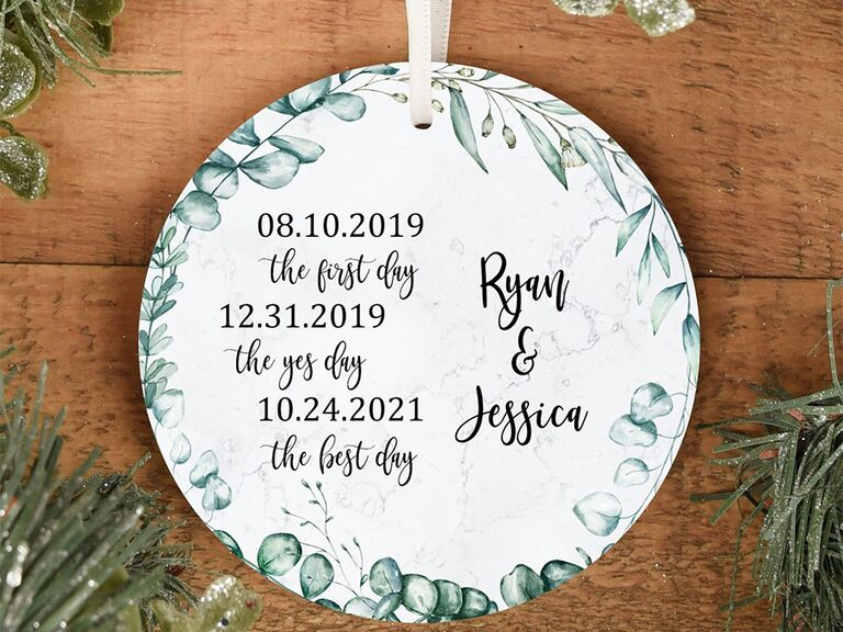 Circle ornament with greenery border and important dates and personalized names in black script