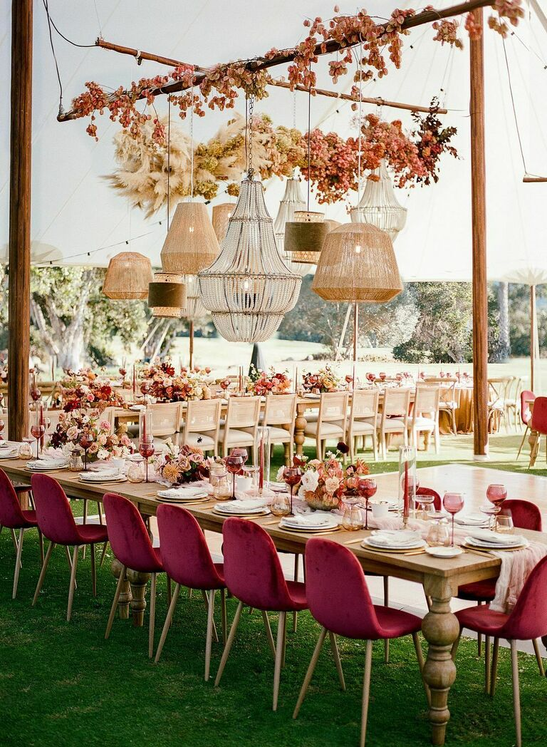 Tented reception with mismatched chandeliers and burgundy velvet chairs