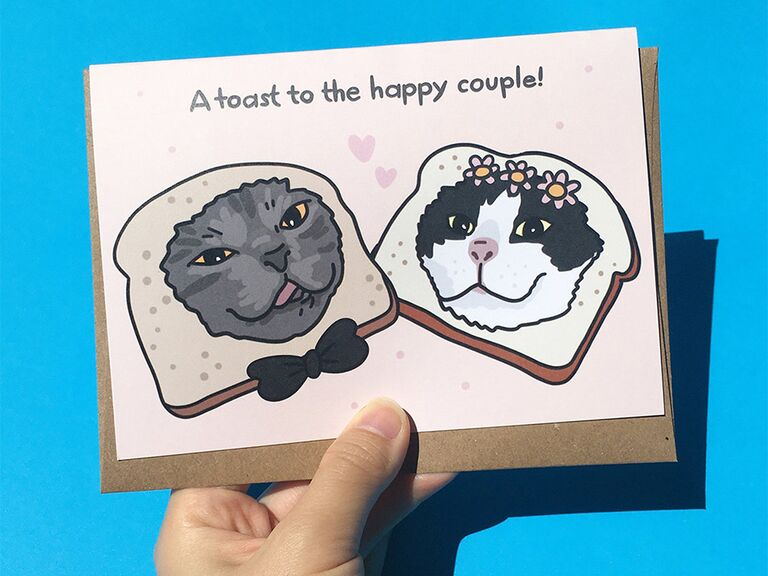'A toast to the happy couple!' in gray type with cartoon bride and groom cat faces in pieces of toast