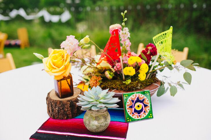 Terra-cotta pots overflowed with succulents, beautiful bold blooms and custom papel picado flags. Table numbers were colorful Mexican tiles.