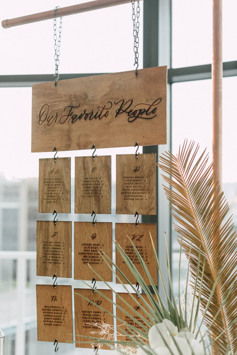 Laser-cut wood seating chart hanging from copper frame