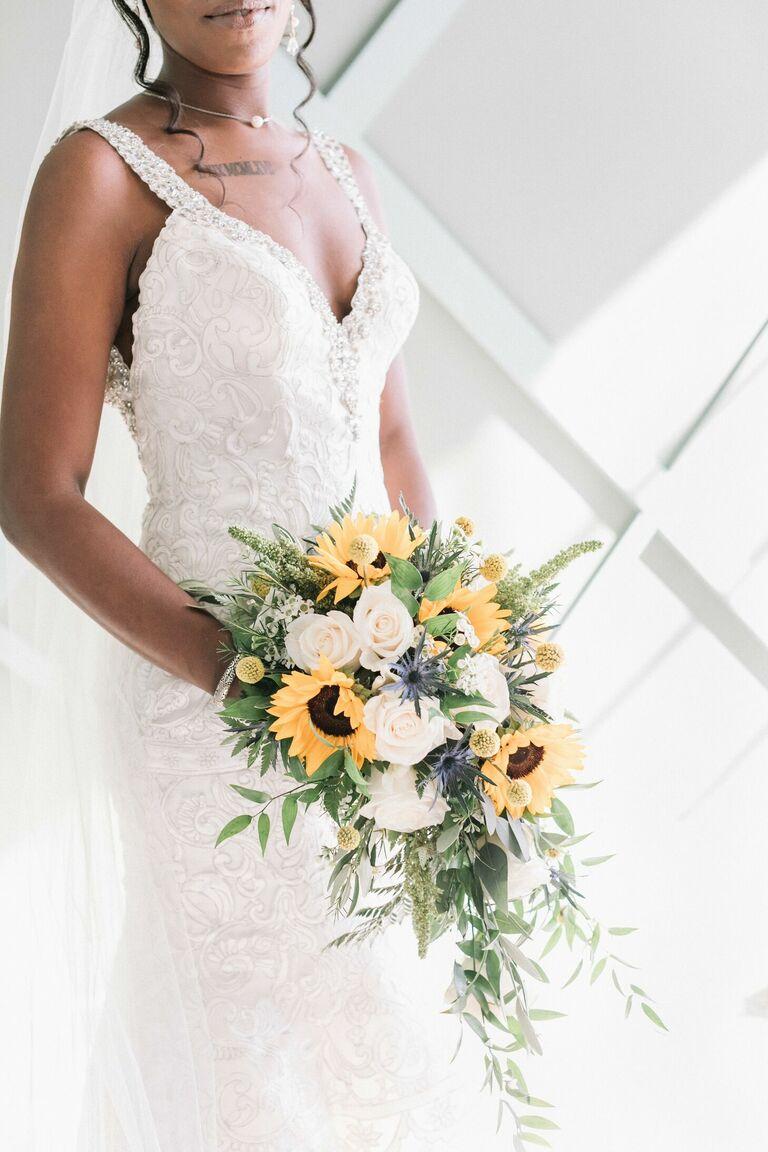 Bride holding rustic cascading sunflower bouquet