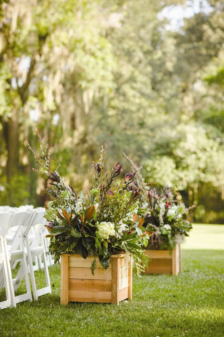 Large planter boxes were filled with magnolia leaves, white hydrangeas and burgundy proteas for a lush, yet rustic look.