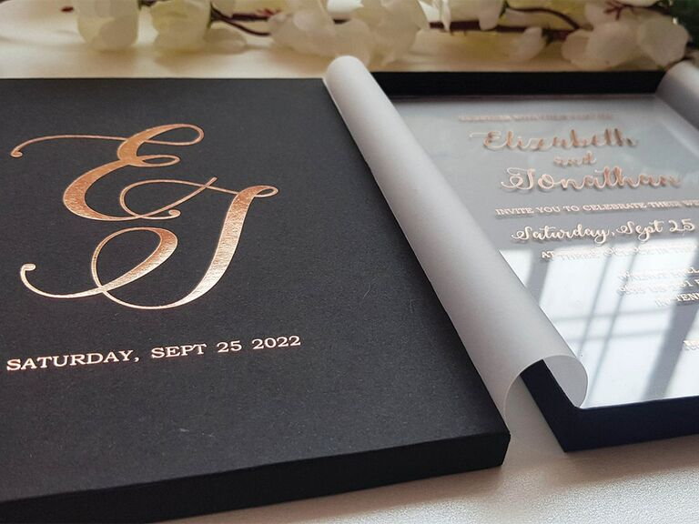 Black box with rose gold calligraphy monogram on outside with acrylic invite