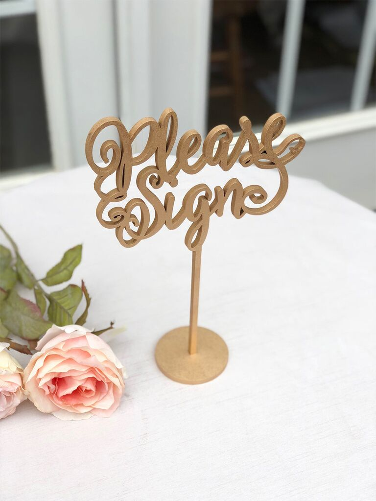 'Please sign' wood cut out in loopy script
