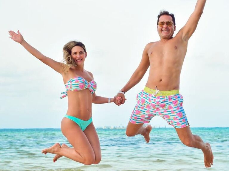Couple jumping in the air wearing matching two-piece and trunks with watermelon print