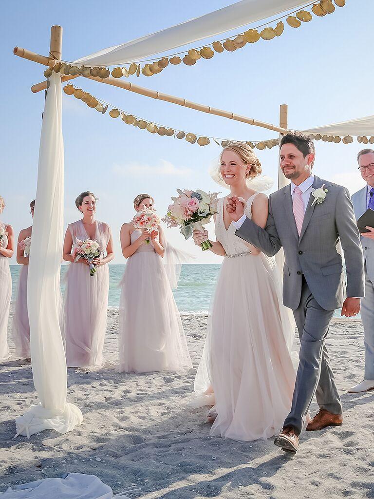 Beach wedding arch decor with linen fabrics and seashells