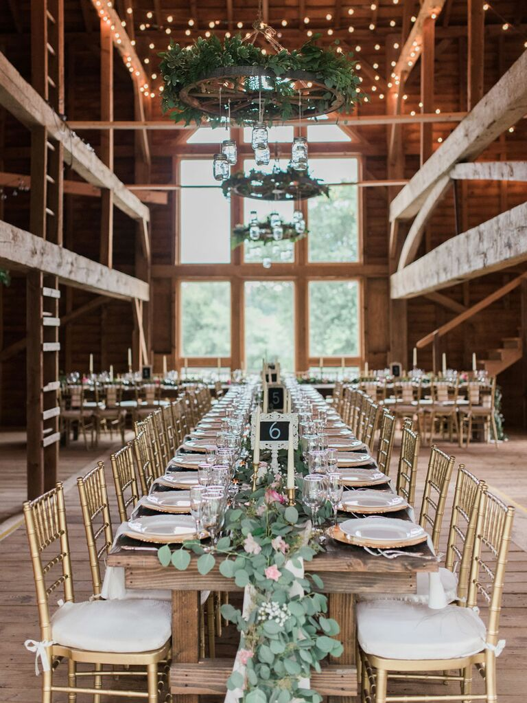 Rustic barn wedding with greenery garlands as table runners