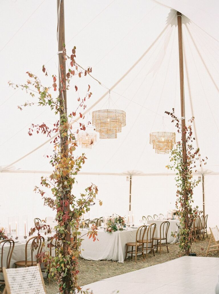Tented wedding reception with foliage and chandelier decorations
