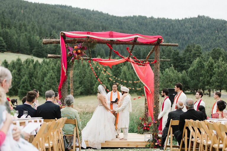 Couple exchanging vows beneath wood mandap in the mountains
