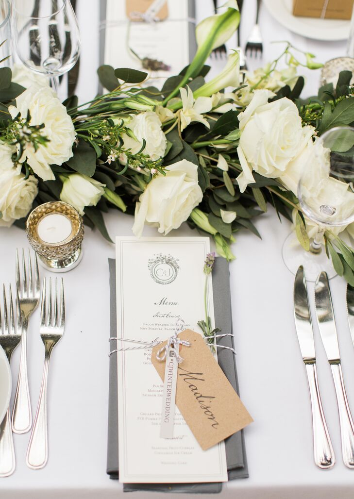 """Dining tables were decorated with ivory roses accented with greenery, with simple black and white menus at each setting. """"I had designed the menus to sit on top of a folded napkin, tied with twine, a name tag and a lavender sprig,"""" Christine says."""