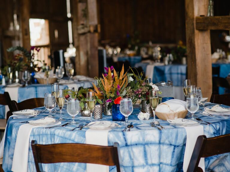 Blue and white tie-dye tablecloths at rustic barn wedding reception