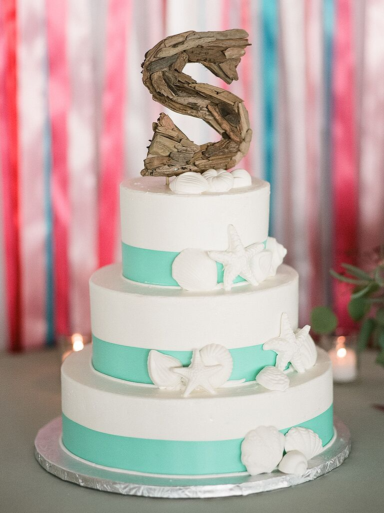 Three tiered white wedding cake with navy anchor and rope knot