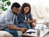 Engaged couple planning and budgeting for honeymoon.
