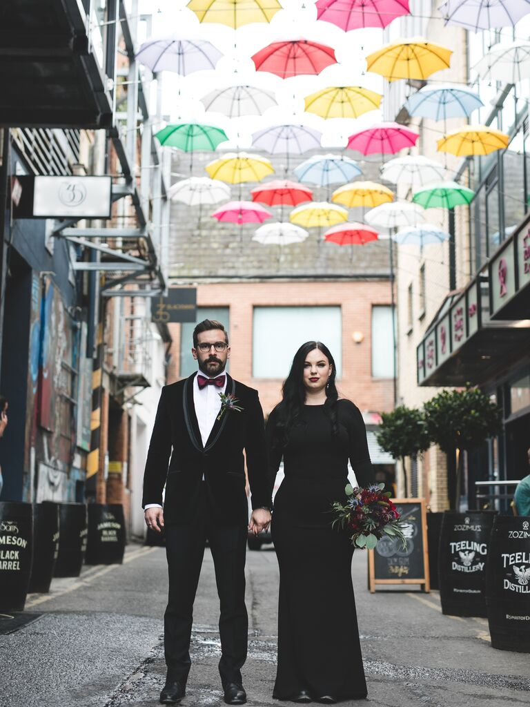 Couple holding hands in front of umbrellas