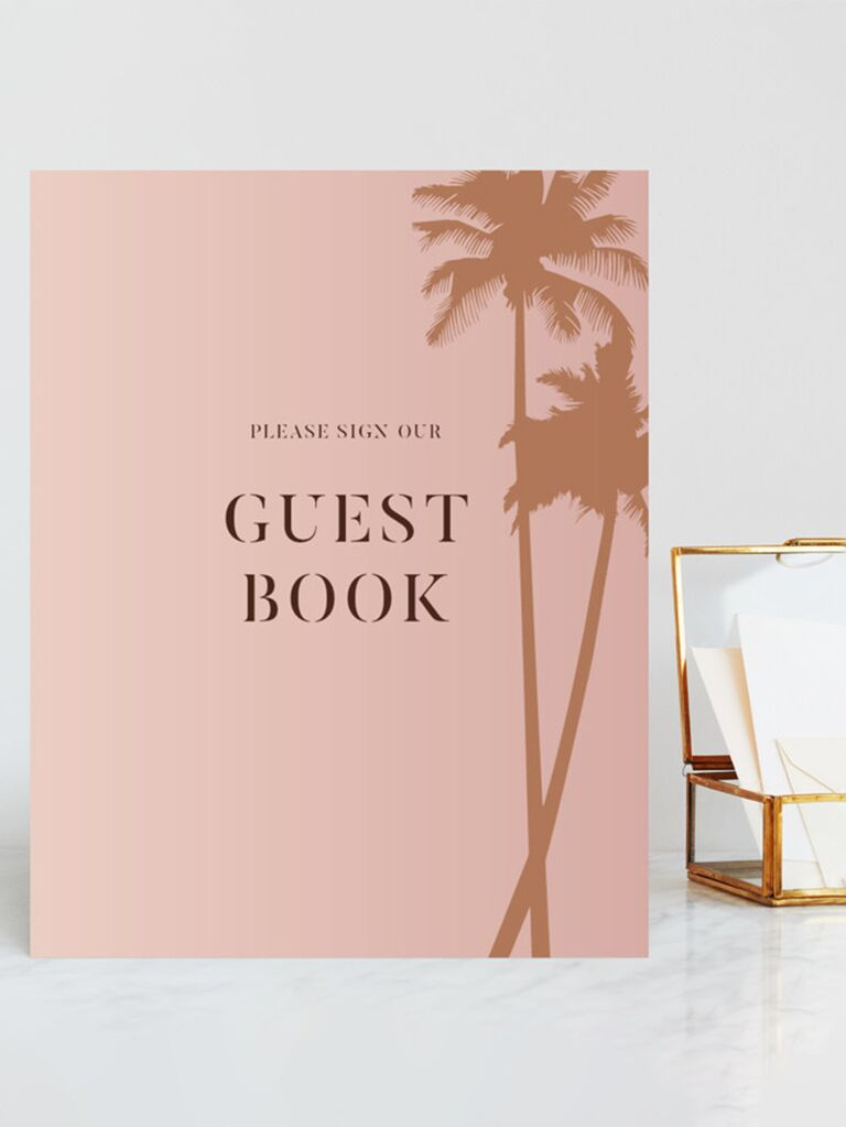 'Please sign our guest book' in minimalist type with gold palm tree graphics on right side on pink sign