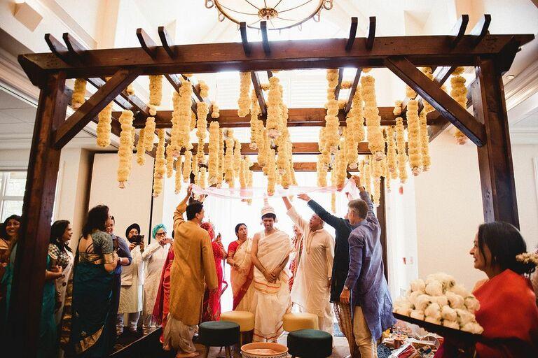 Wedding ceremony taking place beneath wood mandap with orange flower accents