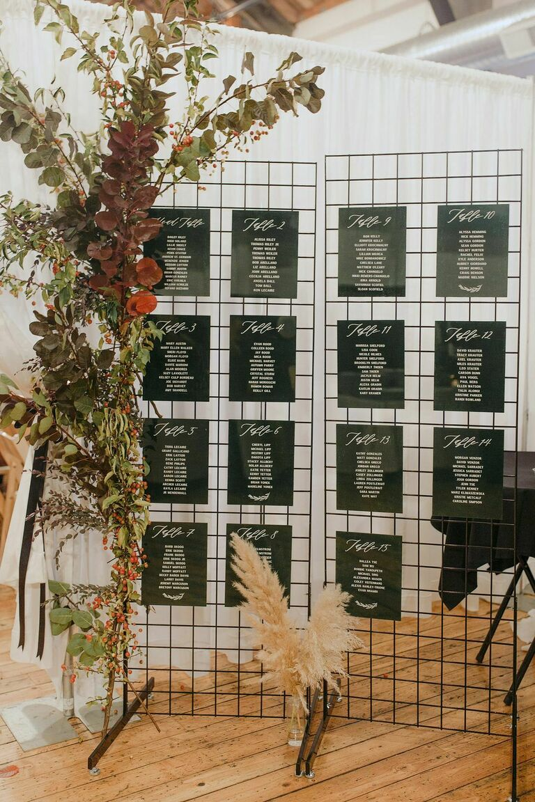 Black seating chart on wire mess frame with flower accents