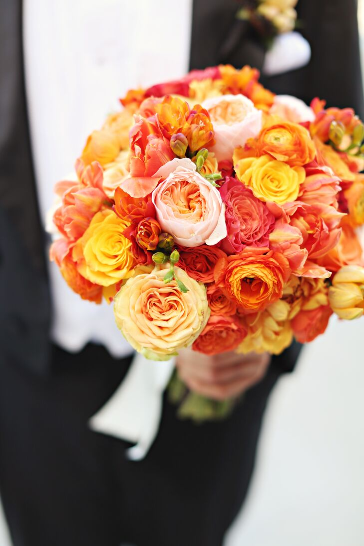 """Kathryn carried a textured orange bouquet of garden roses, dahlias, tulips, spray roses, English roses, freesia and ranunculus. """"With my color palette consisting of all bright, beautiful colors it was important to me that my bouquet look like I was a part of the same story,"""" says Kathryn."""
