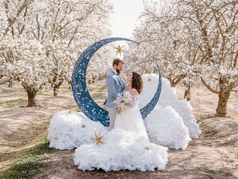 Bride and groom at celestial wedding posing in front of crescent moon with 3D cloud puffs