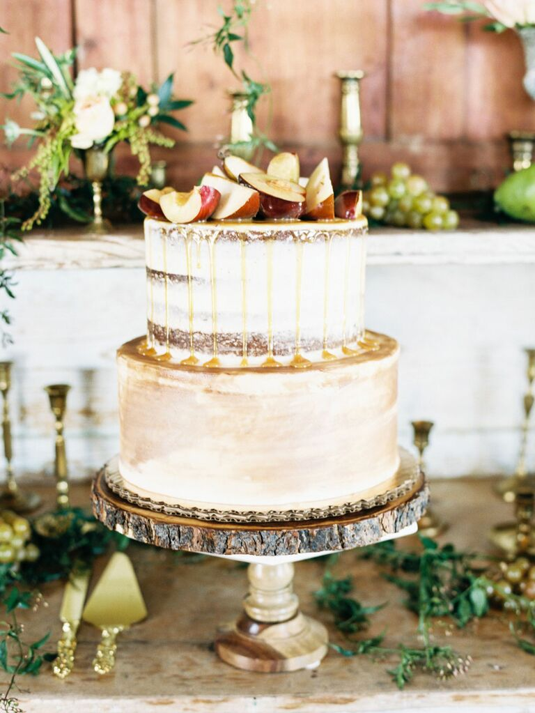 Two-tier rustic cake with apple slices and caramel drizzle on top