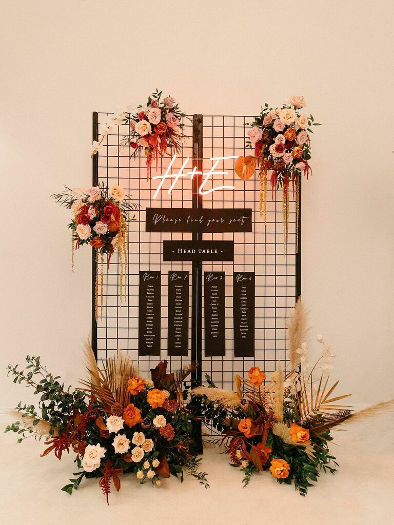 Black seating chart with neon sign and colorful flowers