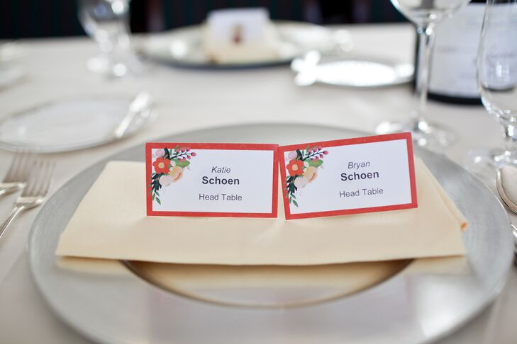 White escort cards were bordered with red, and had a floral graphic in the upper left corner.