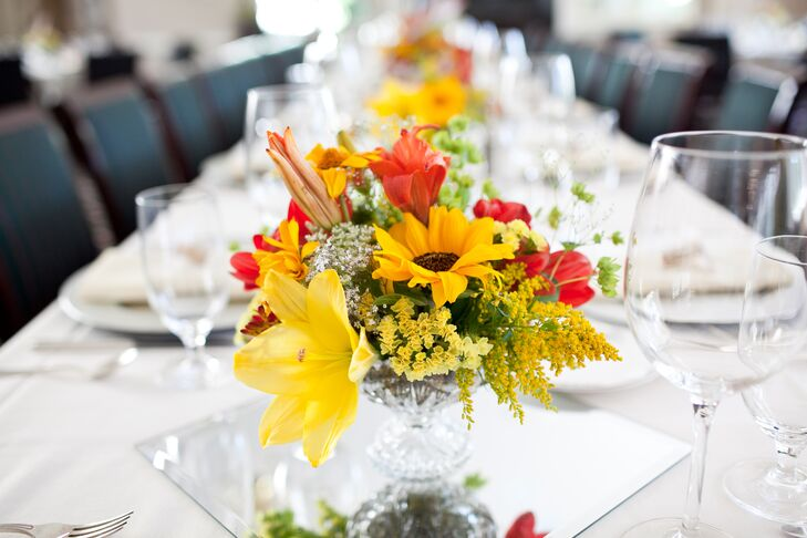 Yellow and red flower centerpieces decorated reception dining tables, filled with summer pickings of sunflowers, lilies and stock.