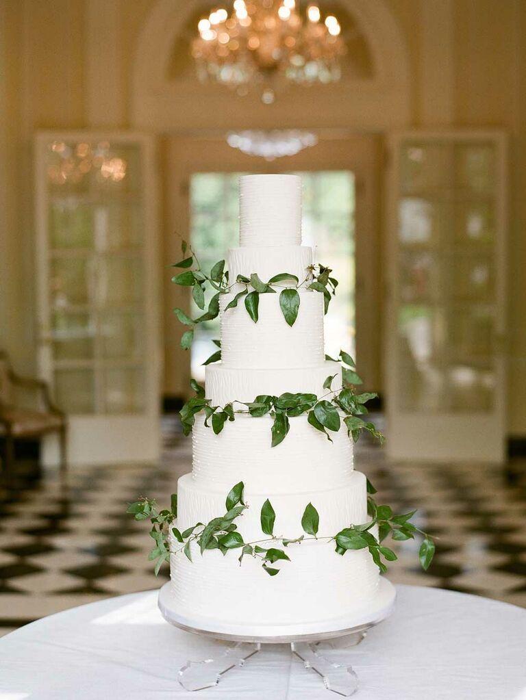 White wedding cake with green leaf garlands