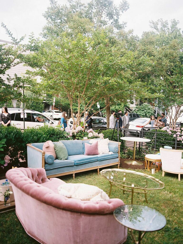 Art deco lounge seating area at wedding reception with velvet pink and blue couches