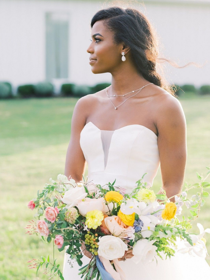 Bride holding yellow wildflower-inspired bouquet