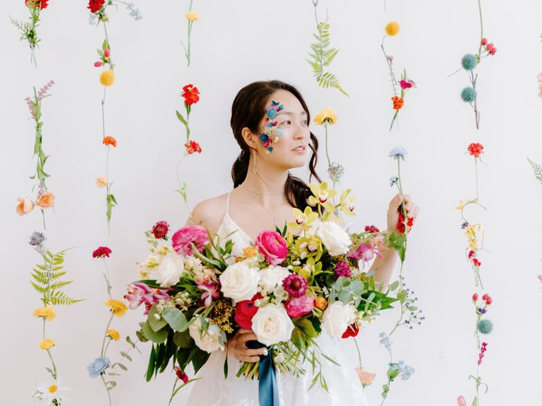 bride stands in front of flower curtain backdrop showcasing wedding colors 2021 bright yellow pink red green