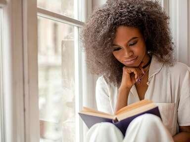 Woman sitting by window reading