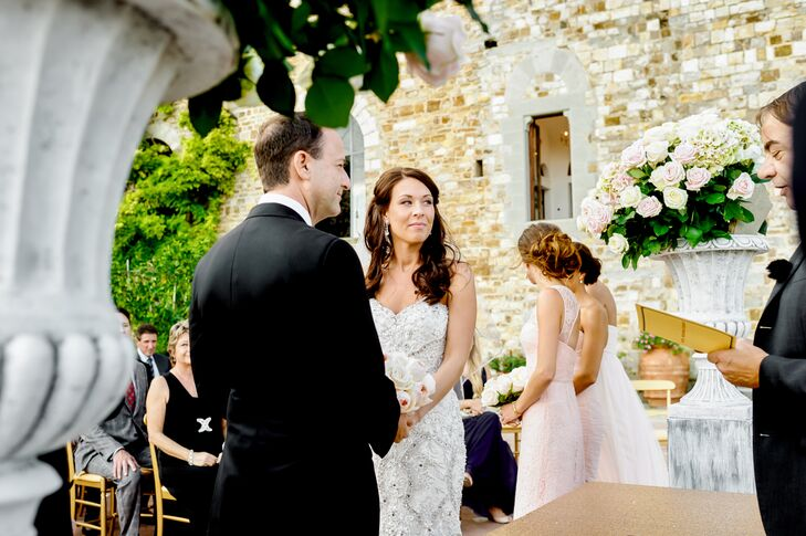 Surrounded by 55 of their closest family members and friends, Lindsay and Robert exchanged vows in an intimate outdoor ceremony at Castello di Vincigliata in Tuscany. Two stone urns overflowing with blush roses and hydrangeas framed the pair as they stood against a backdrop of rolling hills and lush greenery.