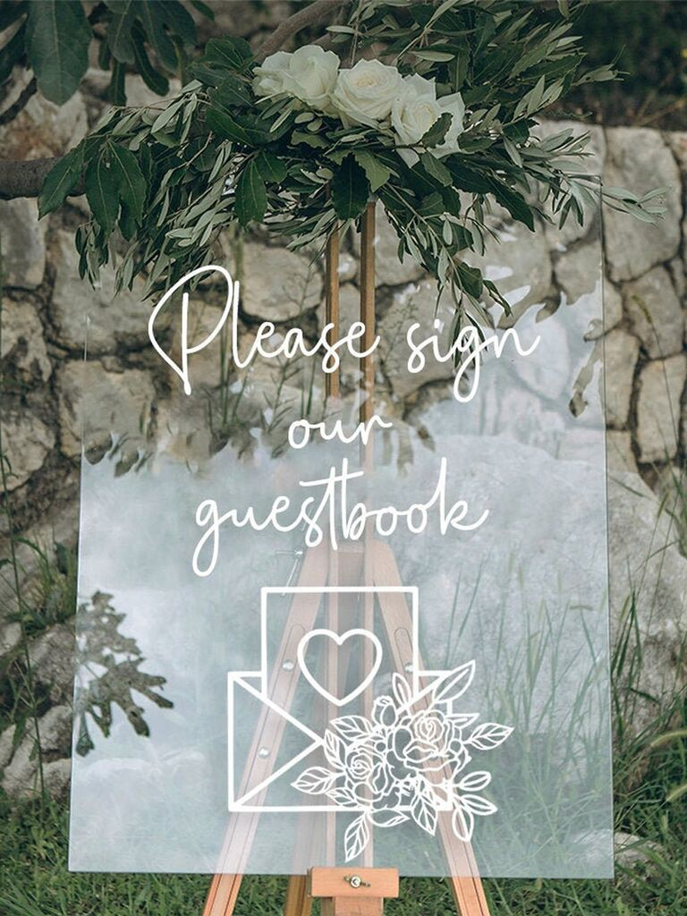 Acrylic sign with 'Please sign our guestbook' in white handwritten script above letter graphic