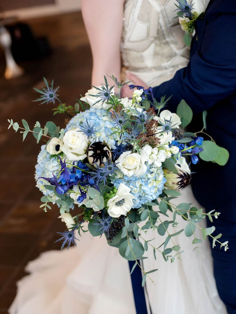 Celestial wedding bouquet with white, blue and indigo florals with greenery sprigs